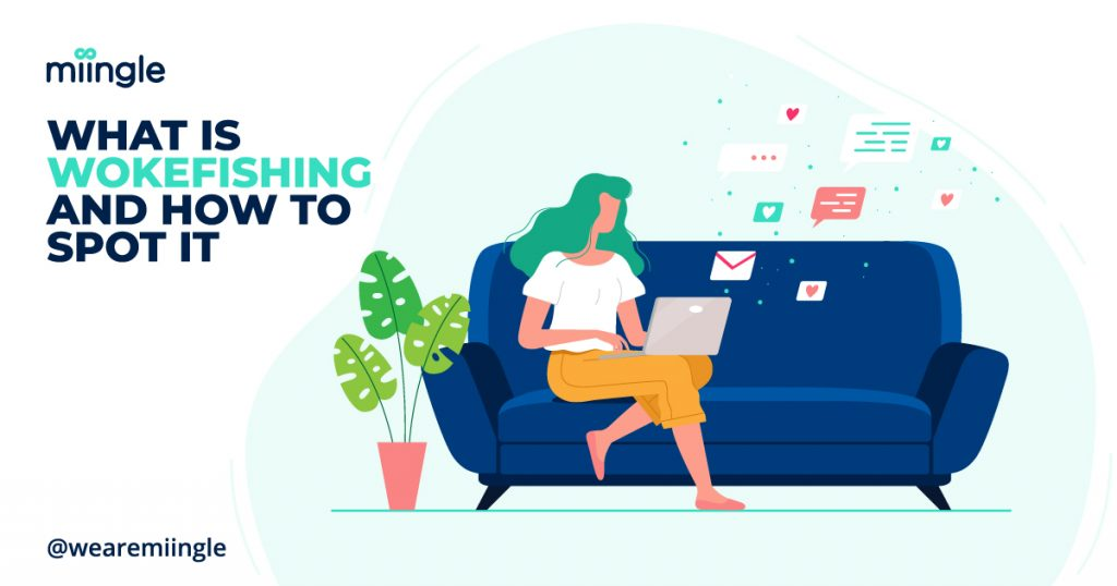 A woman with green hair sitting on a blue sofa browsing the web on her laptop. a monstera plant is on the floor beside her.
