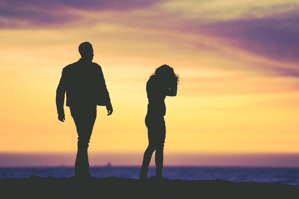 couple walking away from each other with sunset in the background