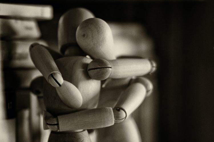wodden-figures-embracing-in-a-hug